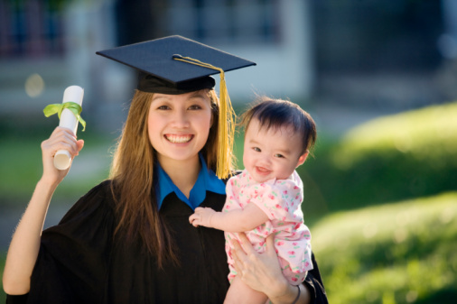 Pretty Asian woman graduate wearing cap and gown holding diploma and baby