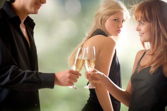 A woman looking behind at her husband who's having an intimate conversation with another woman while drinking