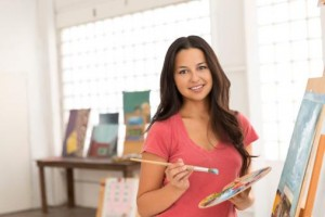 Portrait of smiling woman painting at easel